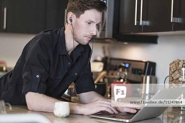 Man working on laptop computer in kitchen