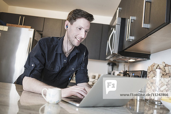 Man smiling while working on laptop computer in kitchen