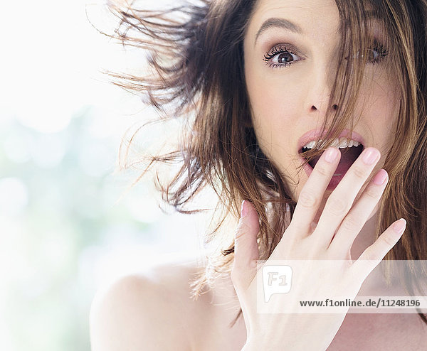 Portrait of surprised beautiful woman with brown hair