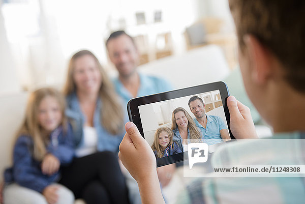 Boy (8-9) photographing family with digital tablet