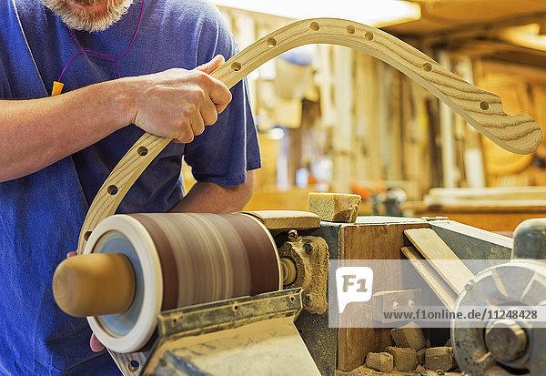 Carpenter polishing wood with sander Carpenter polishing wood with sander