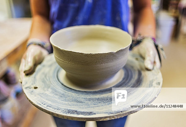female potter holding clay bowl female potter holding clay bowl