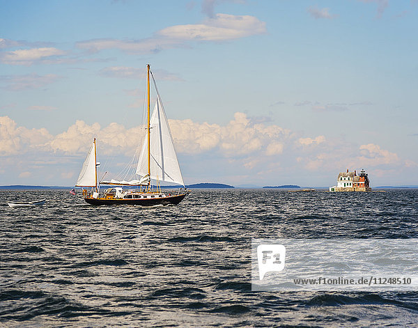 Sailboat in sea and Rockland Harbor Breakwater Lighthouse in distance