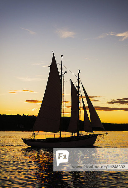 Silhouette of sailboat against sunset sky