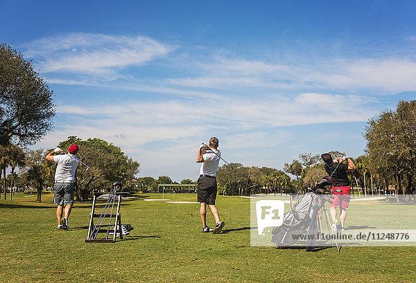 Three men playing golf Three men playing golf