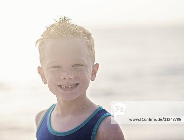 Portrait of boy (6-7) in blue tank top at beach Portrait of boy (6-7) in blue tank top at beach