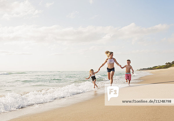 Mother running with boy (6-7) and girl (4-5) on beach by water
