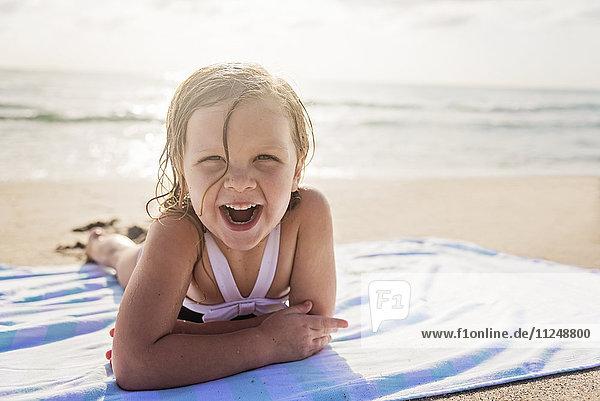 Girl (4-5) lying on beach laughing Girl (4-5) lying on beach laughing