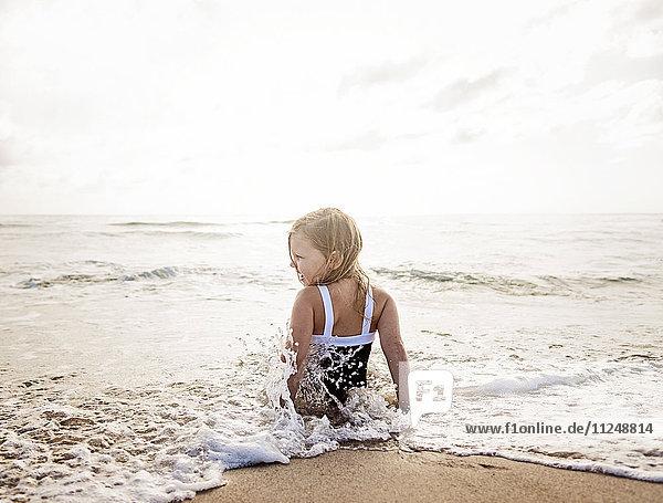 Girl (4-5) sitting in water on beach