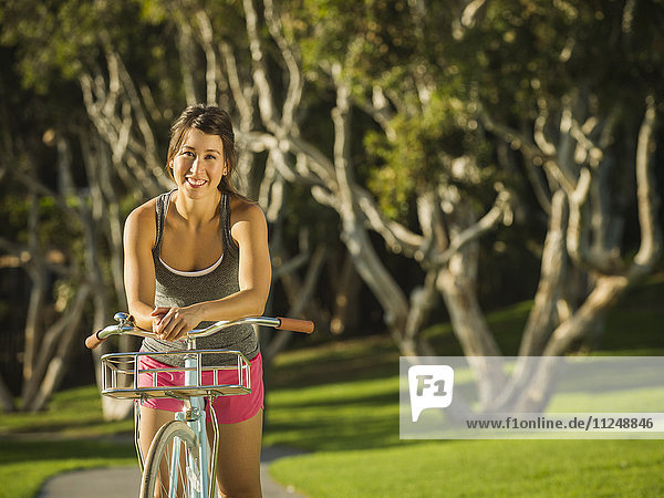 Young woman with bicycle in park