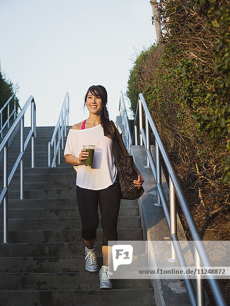 Young woman with smoothie walking down stairs