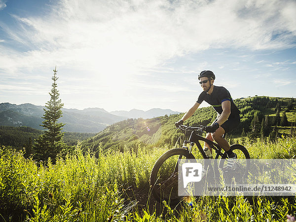 Man during bicycle trip in mountain scenery