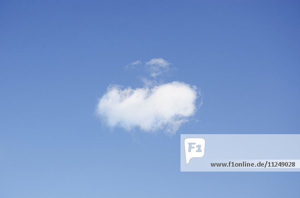 Single cumulus cloud in blue sky