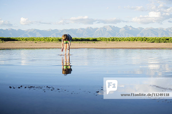 Boy (6-7) wading in water