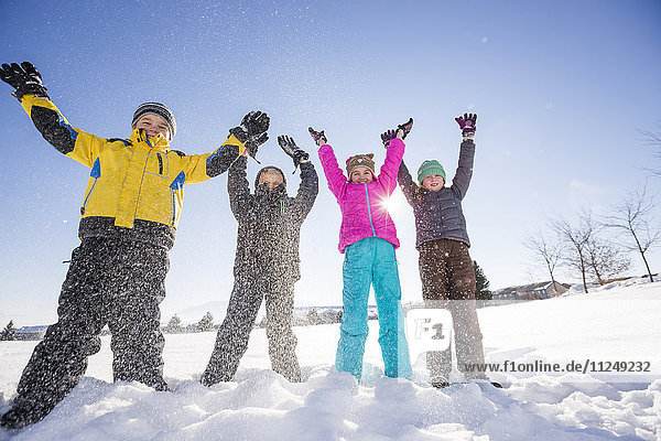 Children (8-9  10-11) standing in snow with arms raised