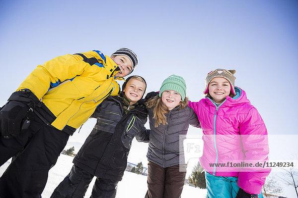 Children (8-9  10-11 ) standing in snow