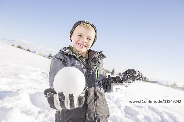 Portrait of boy (8-9) holding snowball