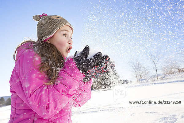 Girl (10-11) in pink jacket blowing snow