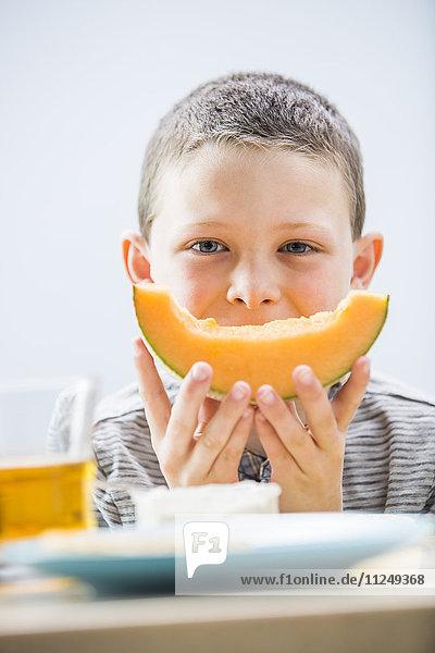 Little boy (6-7) eating cantaloupe for breakfast
