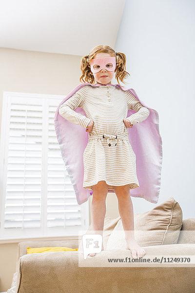Little girl (4-5) playing superman on sofa
