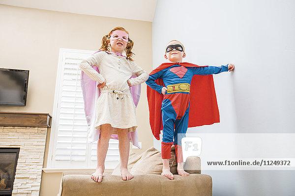 Children (2-3  4-5) playing superhero on sofa