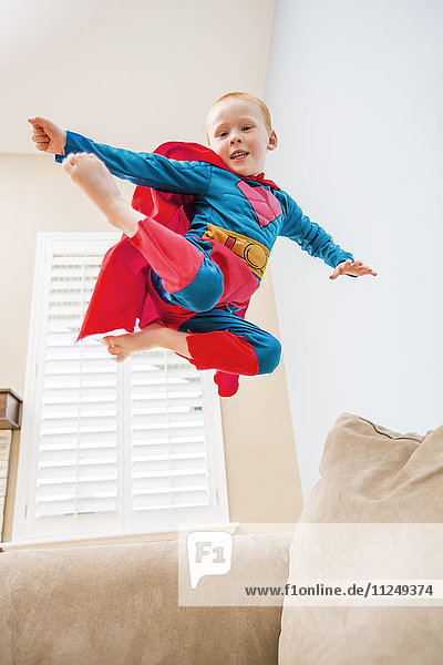 Little boy (2-3) in superman costume jumping on sofa
