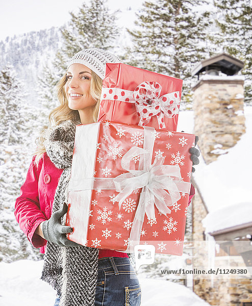 Portrait of young woman holding wrapped presents