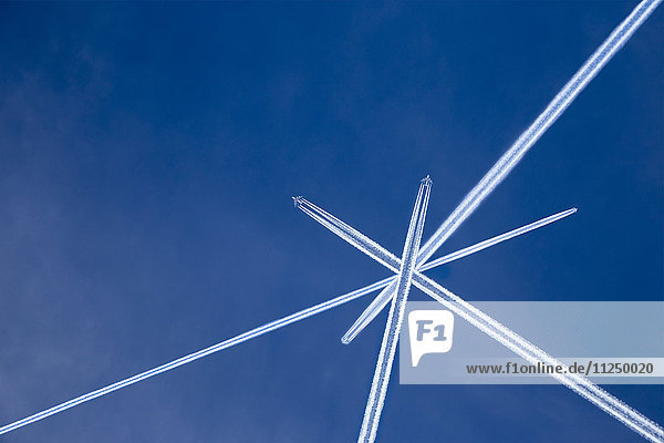 Crossed vapor trails of airplanes in blue sky Crossed vapor trails of airplanes in blue sky