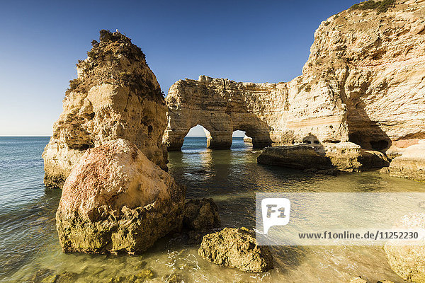 Sunrise on the cliffs and turquoise water of the ocean Praia da Marinha Caramujeira Lagoa Municipality Algarve Portugal Europe