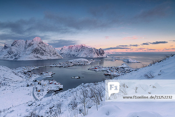 The pink colors of sunset and snowy peaks surround the fishing villages Reine Nordland Lofoten Islands Norway Europe