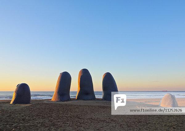 Uruguay  Maldonado Department  Punta del Este  Playa Brava  La Mano(The Hand)  a sculpture by Chilean artist Mario Irarrazabal at sunrise.
