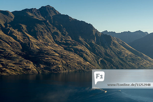 Steamship powers across a dark lake with sharp large mountains  Queenstown  Otago  South Island  New Zealand  Pacific