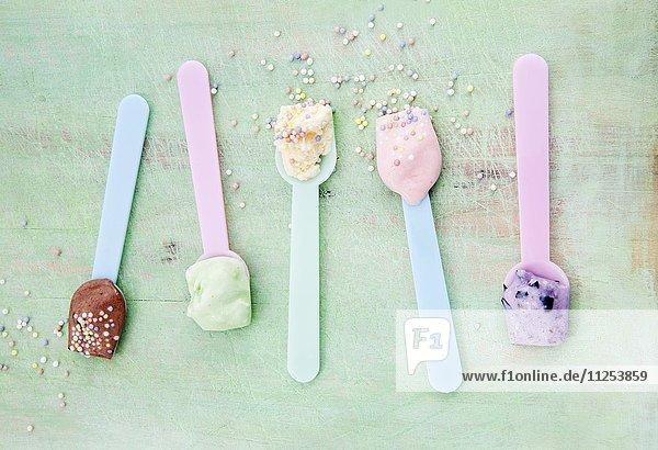 Eislöffel mit verschiedenen Eissorten: Vanille, Erdbeere, Schokolade, Heidelbeere und Minze mit Zuckerperlen