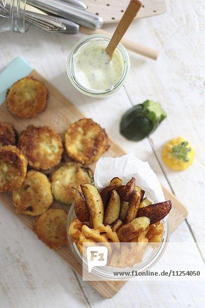 Panierte Zucchinischeiben  Kartoffelspalten und Kartoffelgitter mit Dip