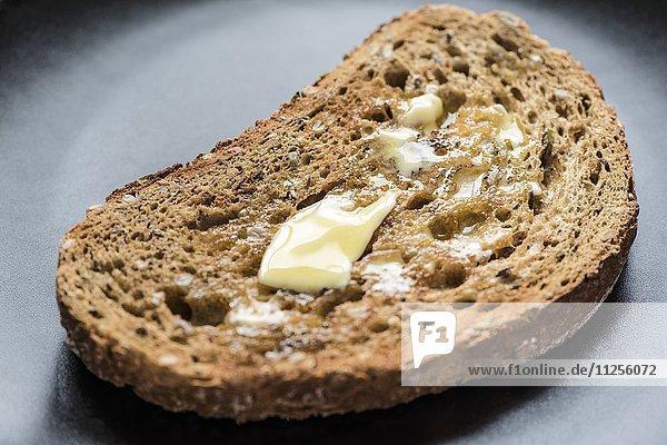 Eine Scheibe Vollkorntoast mit schmelzender Butter