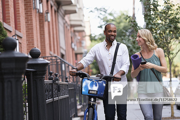 Couple walking with bicycle and exercising mat