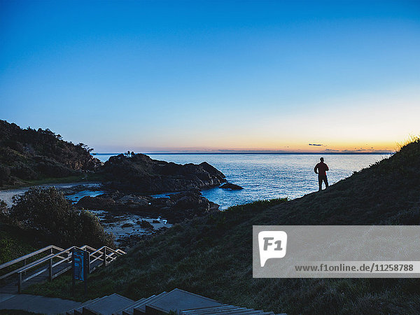 Australia  New South Wales  Port Macquarie  Silhouette of man looking at sea at sunrise
