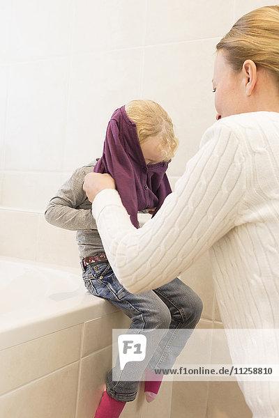 Mother dressing daughter (4-5) in bathroom