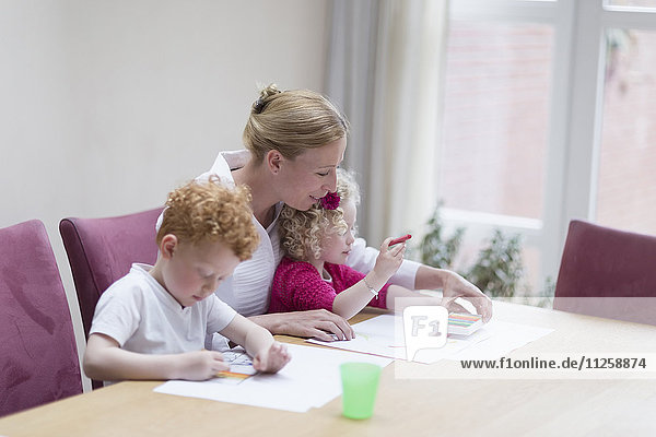 Mother drawing with son (8-9) and daughter (4-5)