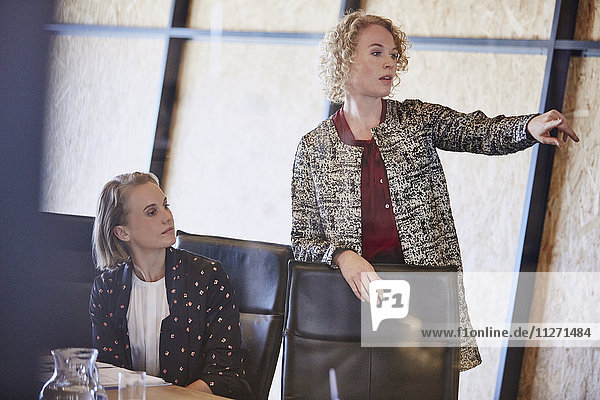 Businesswoman pointing in conference room meeting