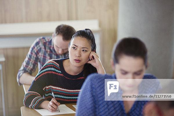 Nachdenkliche Studentin beim Test im Klassenzimmer