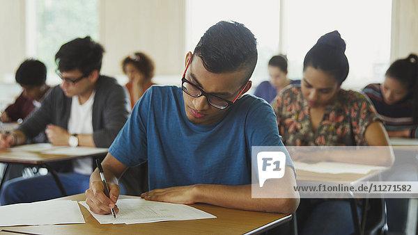 Männlicher Student beim Test am Schreibtisch im Klassenzimmer