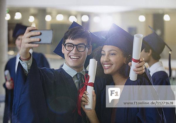 Hochschulabsolventen in Mütze und Kleid mit Diplomen  die für Selfie posieren.