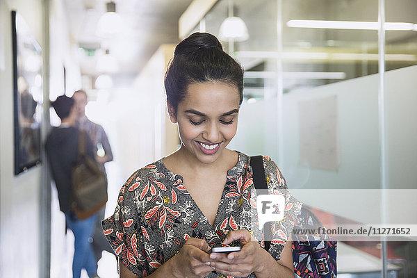 Lächelnde Studentinnen texten im Flur