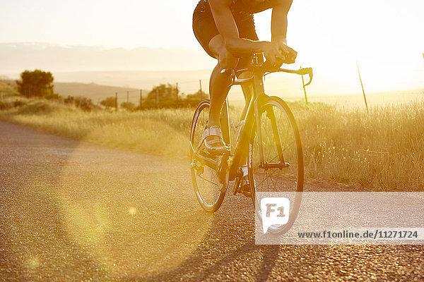 Männlicher Radfahrer auf sonniger Landstraße