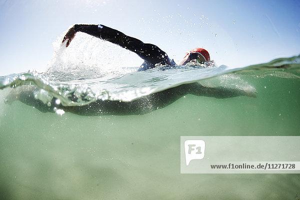 Schwimmender Triathlet im Meer