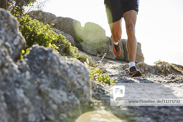 Männlicher Läufer auf felsiger Strecke
