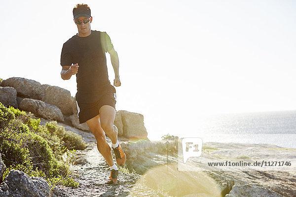 Männlicher Triathlet auf sonnigem Felsweg entlang des Ozeans
