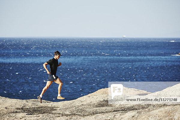 Männlicher Triathlet  der auf dem felsigen Ocean Trail läuft.