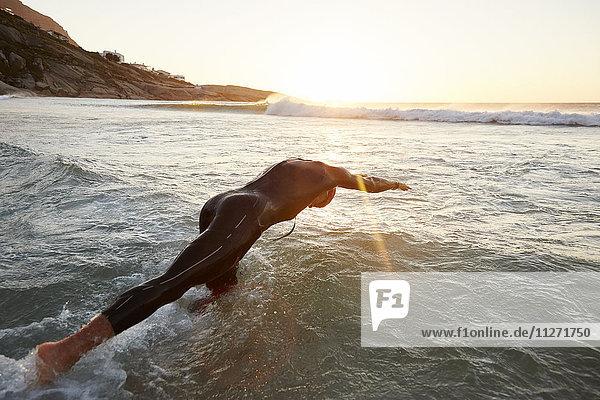 Triathletenschwimmer im Neoprenanzug beim Eintauchen ins Meer